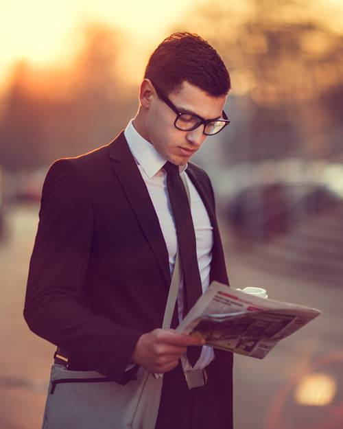 Business man with coffee reading newspaper