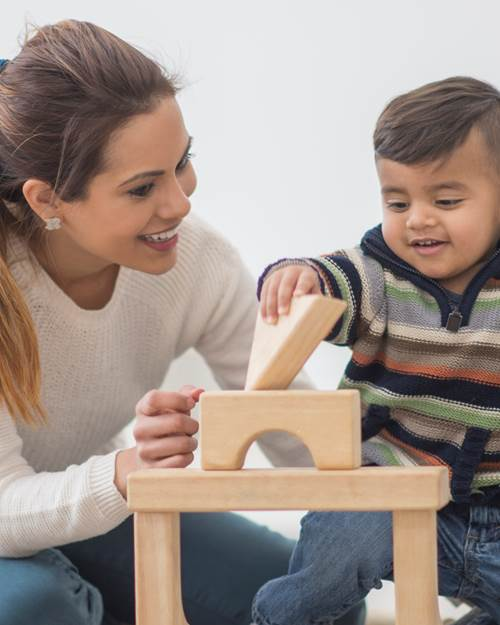 Mother and son stacking wooden blocks