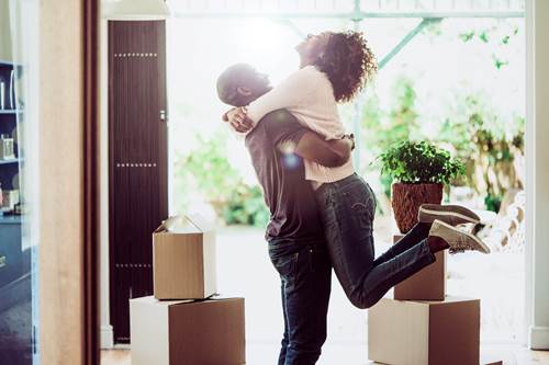 Happy man lifting woman in their new house