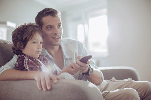 Father and son watching television at home