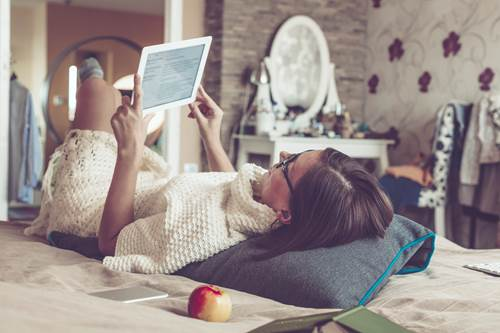 Woman lay on bed reading tablet
