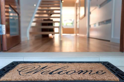 Close up of a welcome mat and an inviting house