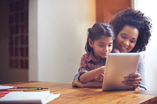 Mother and daughter using tablet together at home