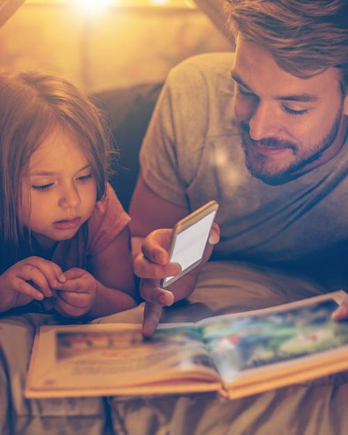 Father reading bedtime story to daughter
