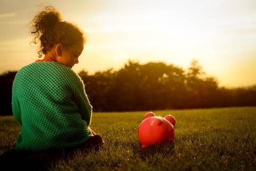 Little girl enjoying the sunset with her piggy bank