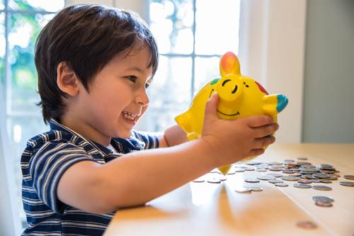 Child playing with piggy bank