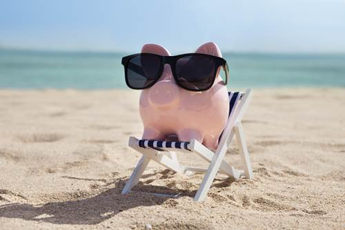 Piggy bank on beach with sunglasses on