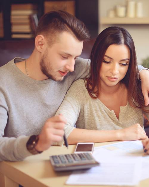 Young couple calculating expenses at home