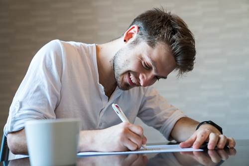 Happy man completing forms at table