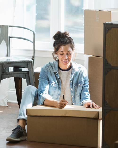 Young woman moving, writing checklist