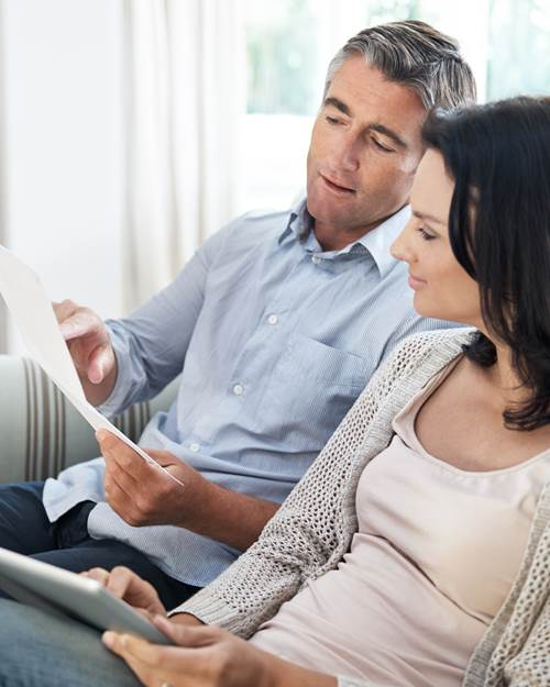 Middle aged couple at home making joint decision