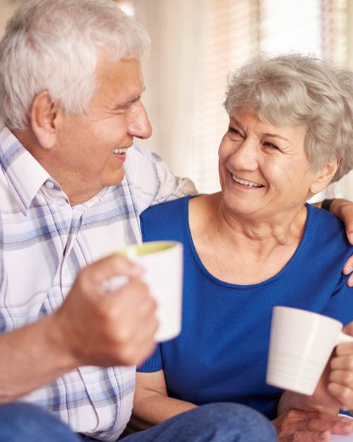 Elderly couple drinking coffee at home