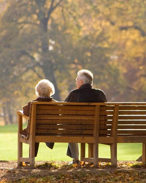 Older couple sat on park bench