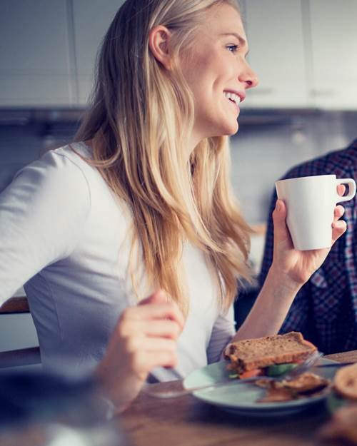 Man and woman eating breakfast together at home