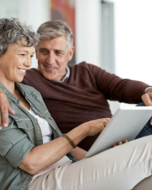 Retired couple looking at mortgages on sofa