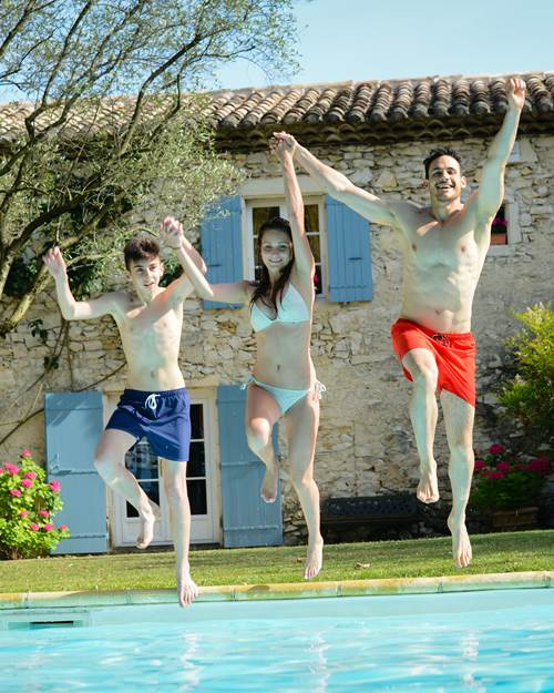 family jumping in swimming pool