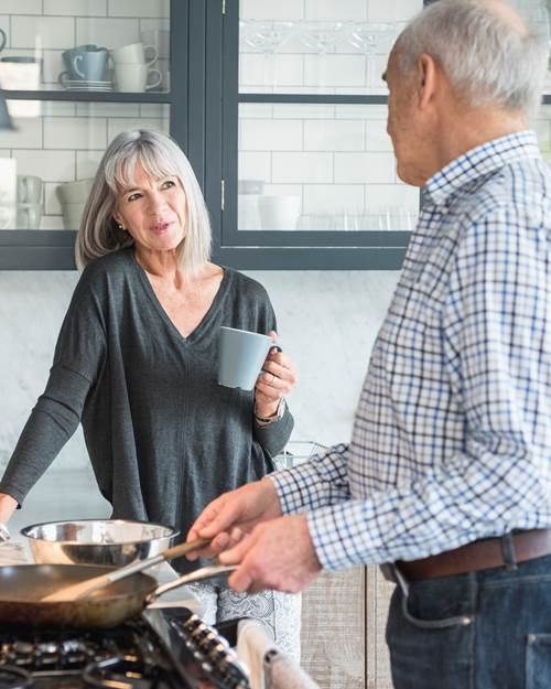 Retired couple cooking together at home